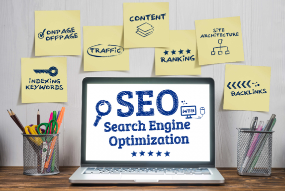 """Laptop displaying """"SEO"""" and surrounded by post-it notes to represent inbound marketing strategy"""