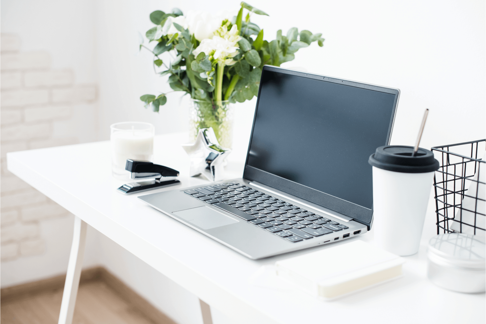 Bloggers workplace, laptop and flowers on a white table top to demonstrate content optimisation