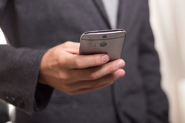 Man in black coat holding smartphone