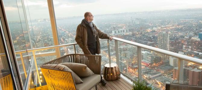 Man looking off balcony at city