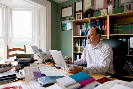 man_working_in_cluttered_home_office