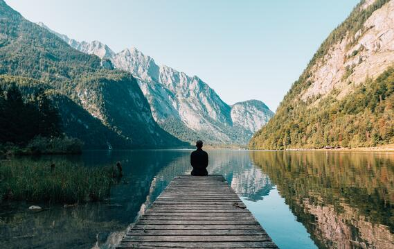 """Figure by lake, surrounded by mountains. For an article about """"Rethinking humanity""""."""