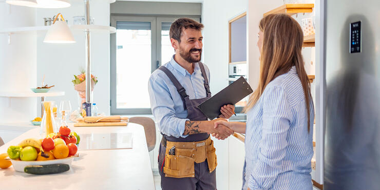 Contractor meeting client in their home by shaking hands