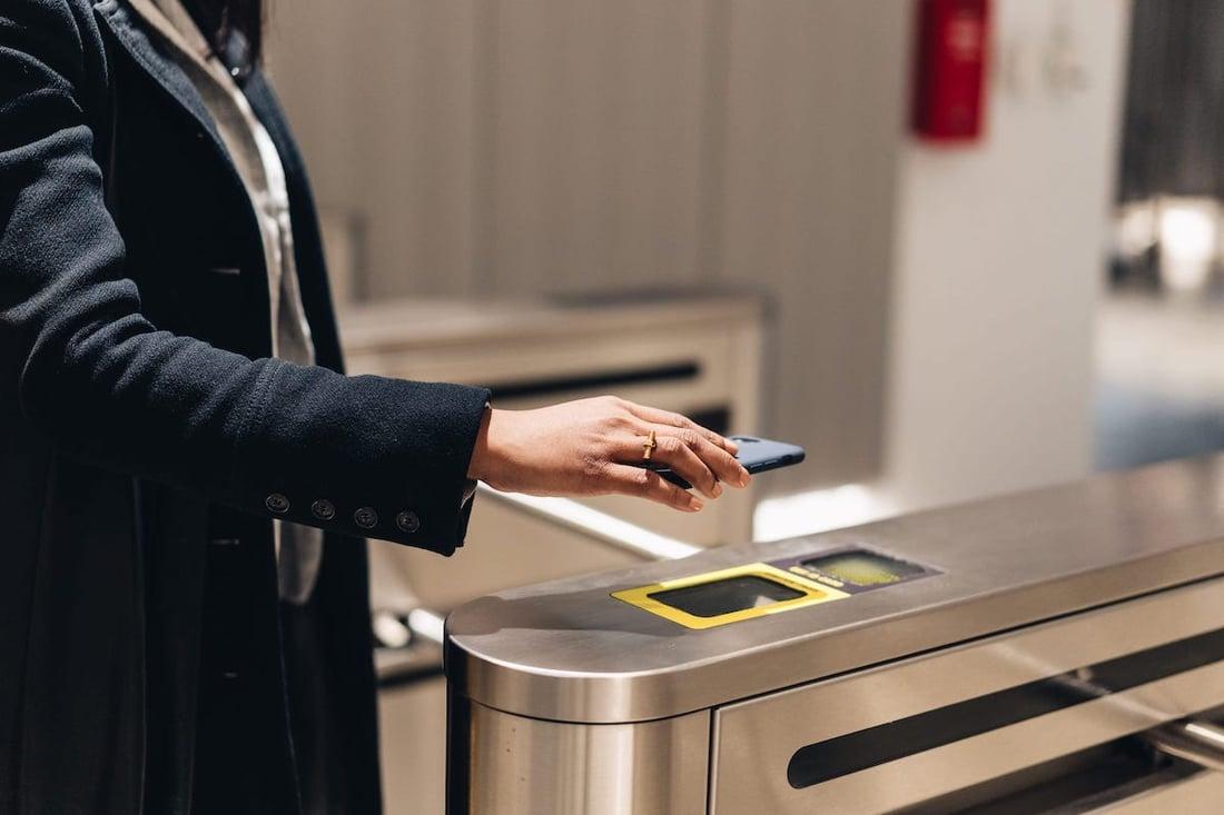 Girl scanning QR code iPhone turnstile