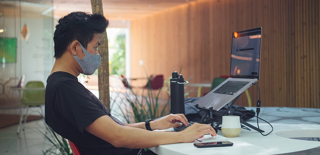 man working in office with mask laptop