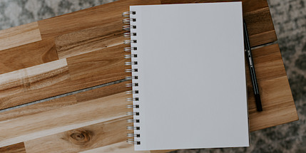 blank notebook on a wooden desk
