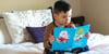 niño leyendo cuento en su cama