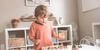 little boy playing with wooden montessori toy