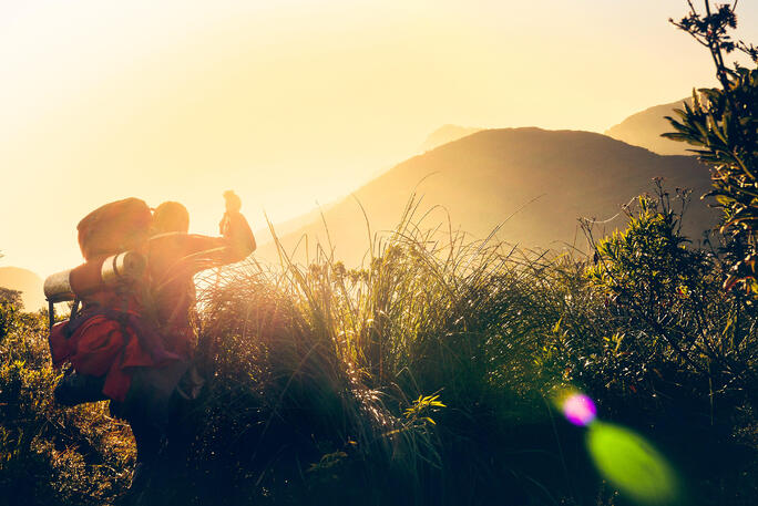person hiking with large backpack in silhouette