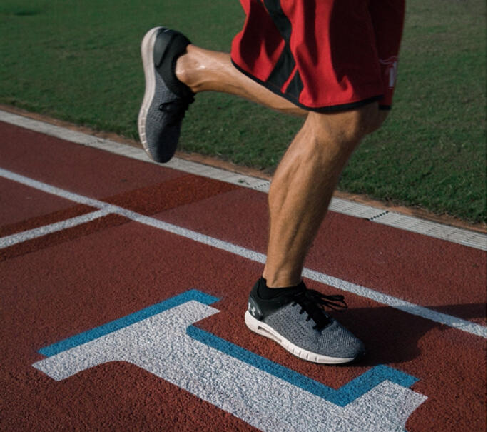 legs of male athlete running on a track