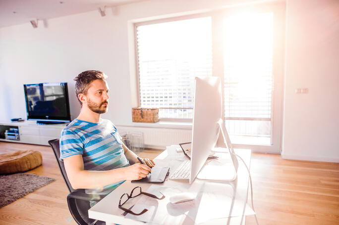 Man sitting at the desk working from home on computer