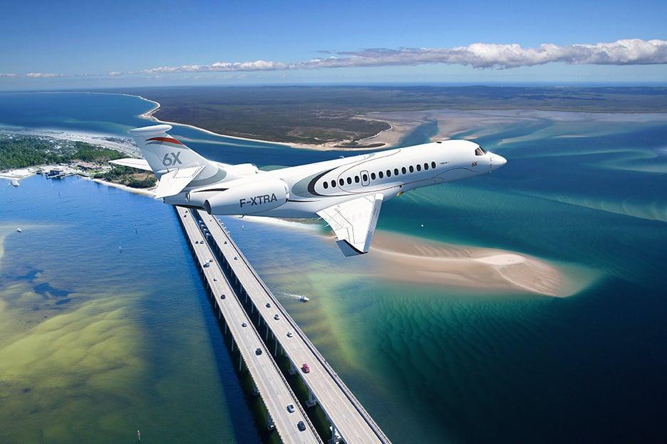 Dassault Falcon 6X flying over highway