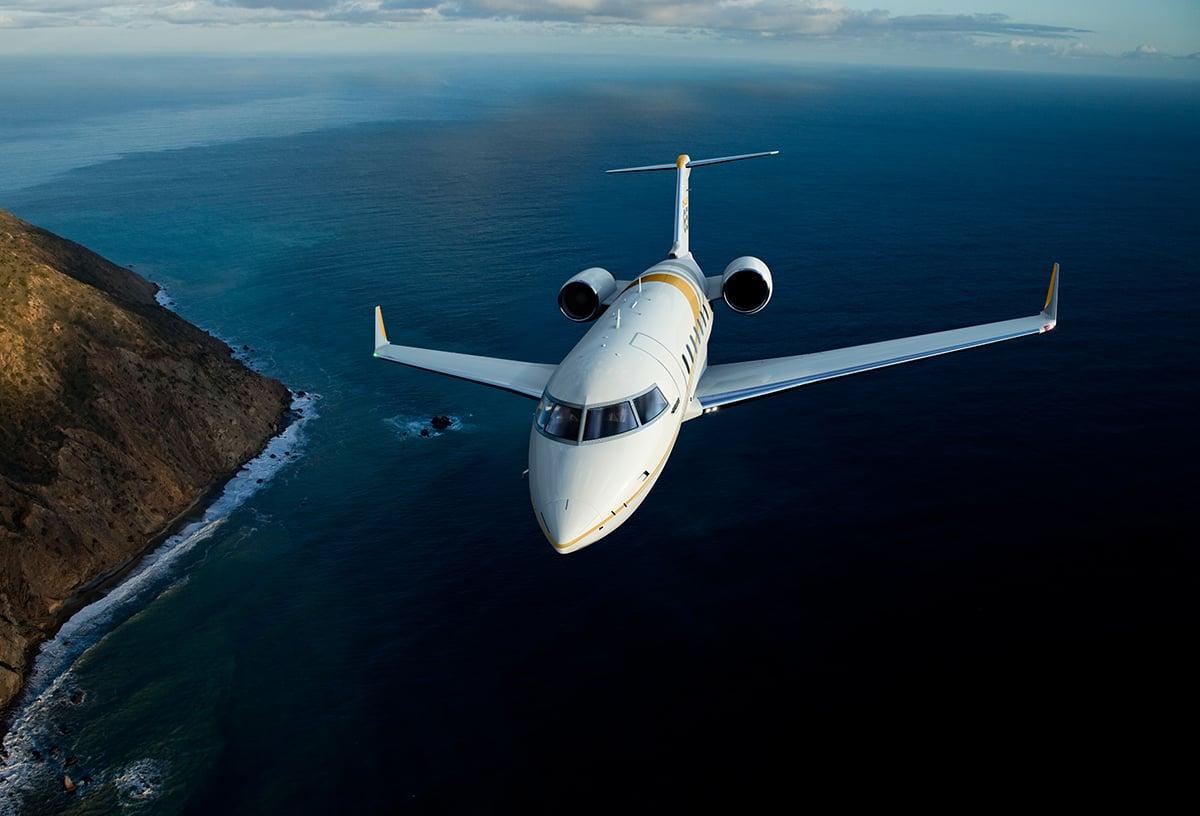 bombardier challenger 650 in flight over water