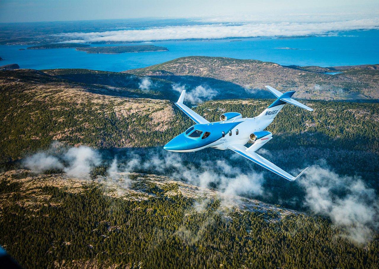 corporate hondajet elite flying over mountains