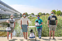 """Dr. Silke Göttler of the Biogents AG (Regensburg) and members of HNU's DigiHealth Institute with a """"BG-Trap Station"""" including an electronic mosquito counting module (in front) and two mobile BG-Pro traps at the HNU lake."""