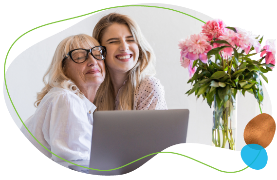 happy grandmother hugging granddaughter on a laptop