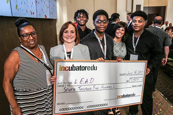 Students and teacher with check