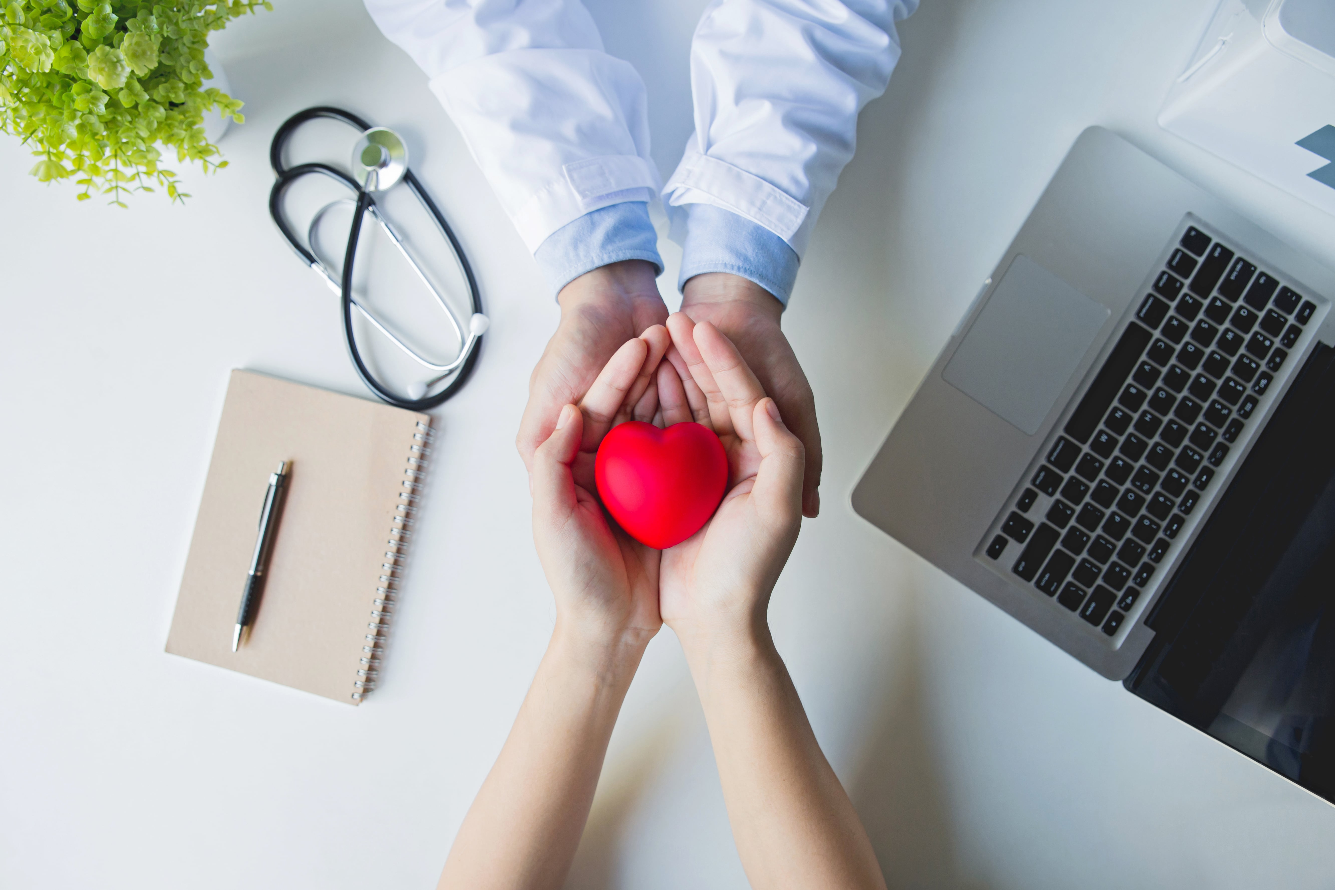 top-view-doctor-patient-hands-holding-red-heart-white-table-min