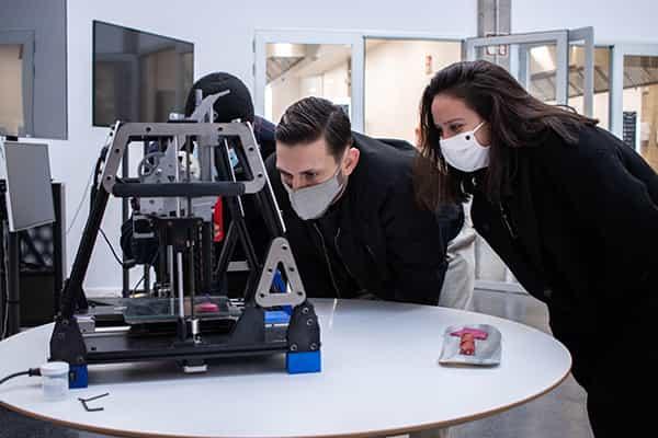 alumnos mirando una impresora 3D carne vegetal