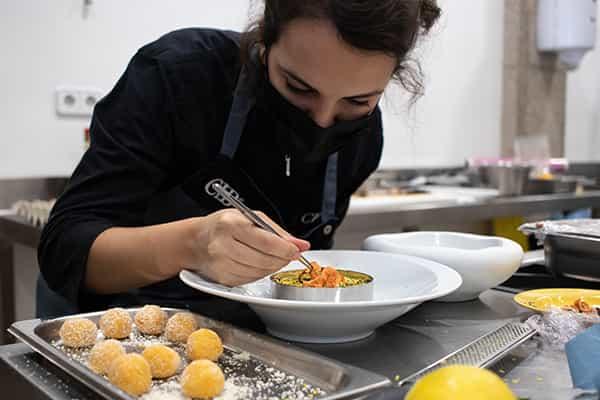 Alumna del Culinary Institute of Barcelona emplatando un plato de comida creativo
