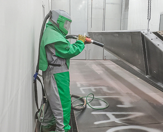 painter in epoxy paint booth
