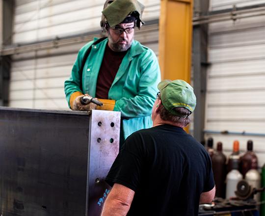 welder and worker in steel shop