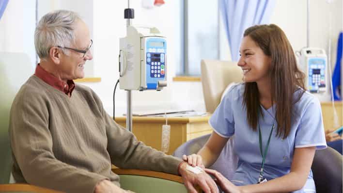 doctora joven conversando con un paciente de quimioterapia