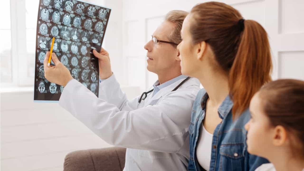 doctor examinando radiografia del cerebro junto a una niña y su madre