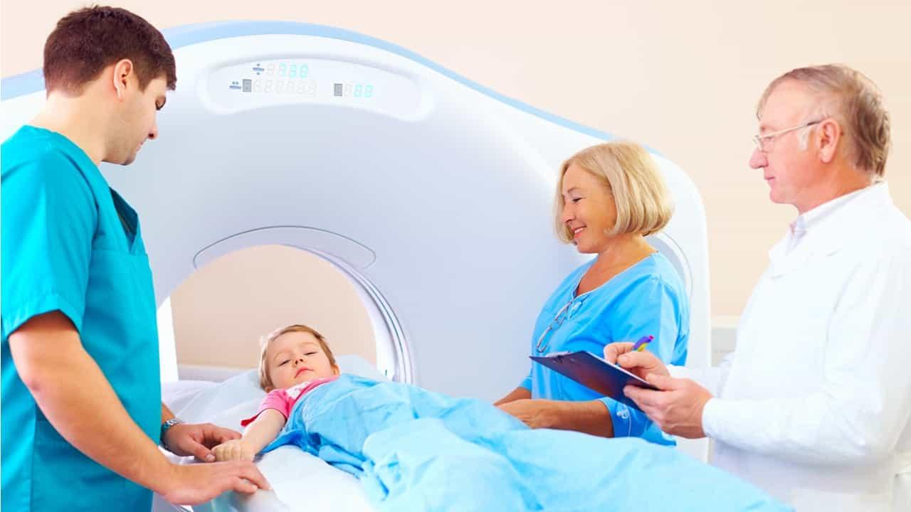 niño con personal medico sometiendose a un tratamiento de radiacion