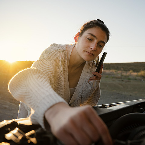 Woman fixing broken down car