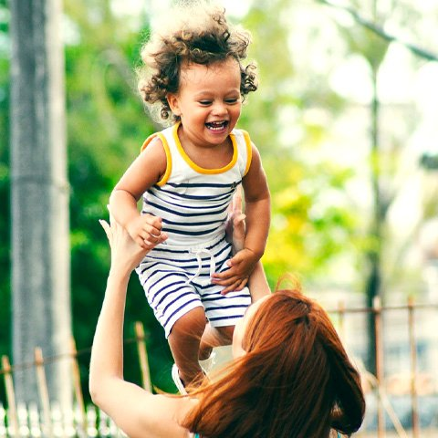 Woman throwing her baby in the air