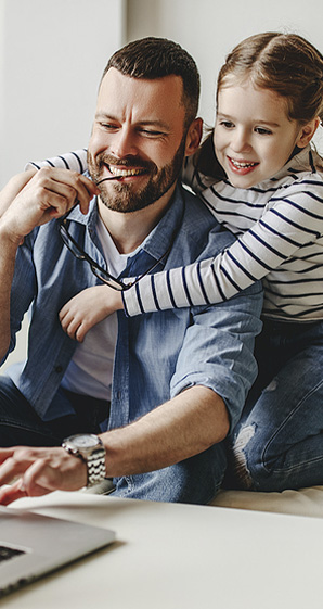 happy father working at computer with his daughter