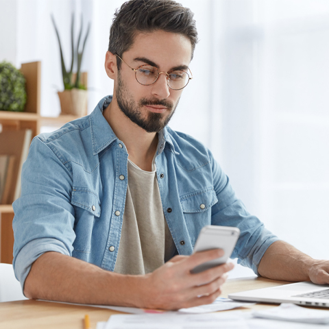 man on working on laptop taking break to look at cellphone-1