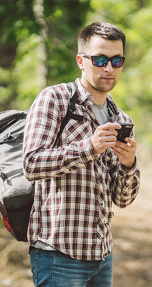 man on hike stopping to use his phone