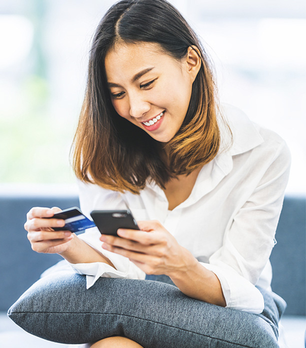 young asian woman using smartphone and credit card