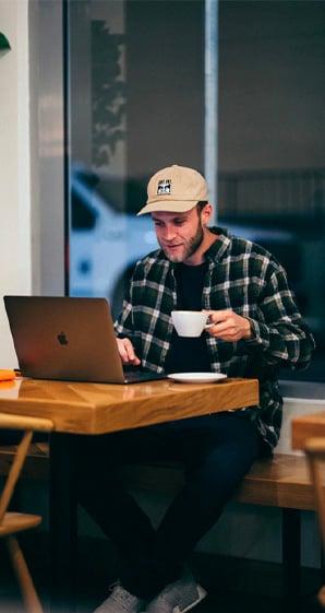 man sitting while having coffee on his laptop