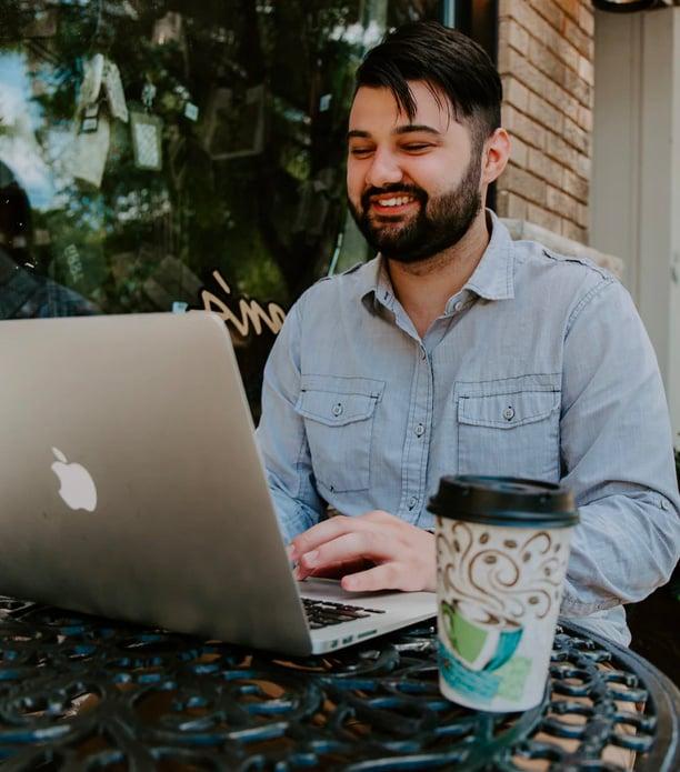 man in gray denim dress shirt on his laptop