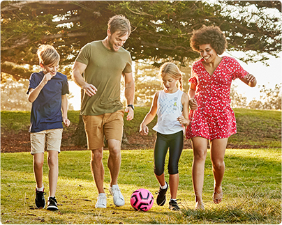 young couple and 2 kids playing soccer in park